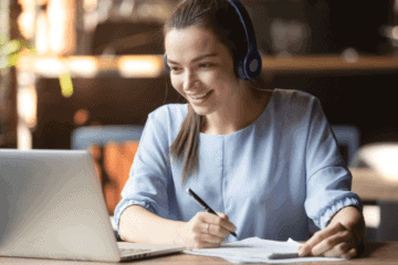 women at computer learning with headphones on